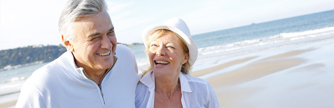 Older couple laughing and walking on beach.